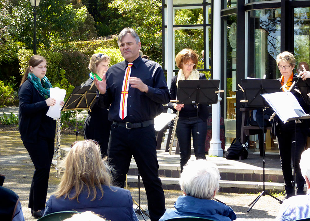 Biberach's Flute Choir performing at Candie Gardens, with conductor Andreas Winter wearing his Guernsey flag tie