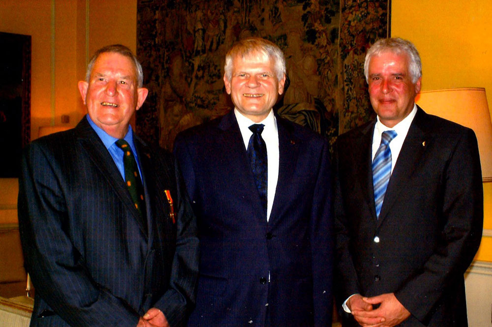 Chris Day, receiving the Cross of the Order of Merit of the Federal Republic of Germany from the German Ambassador, Georg Boomgaarden, (centre), accompanied by Biberach's Mayor, Thomas Fettback